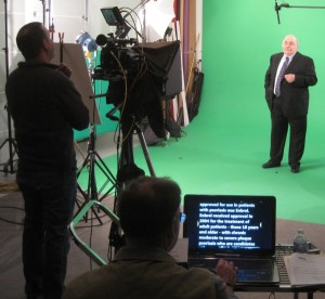 Teleprompter operator, cameraman and talent on the green scree video production set.