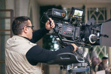 Camera operator with modern professional equipment working during film shooting